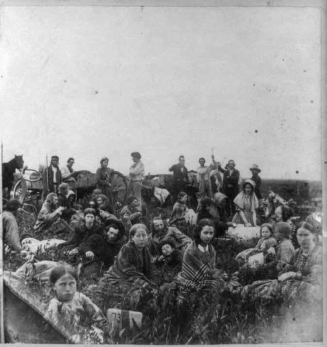 White refugees from Dakota attacks. The four girls closest to the camera in the front are (left to right) Sophia Robertson, Martha Williamson, Anna Riggs, and Nancy Williamson. Martha T. Riggs is the woman kneading dough in the background. The photograph was taken by Adrian J. Ebell.
